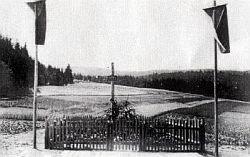 Dřevěný kříž nad společným hrobem nacistických obětí